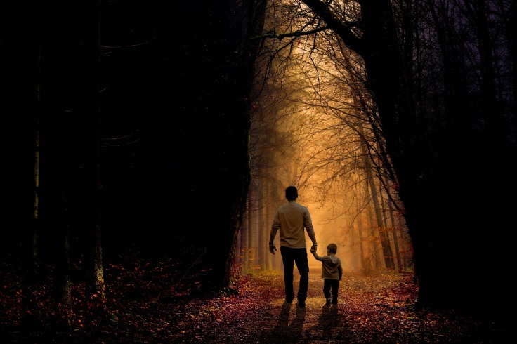A father and son walking in the woods together.