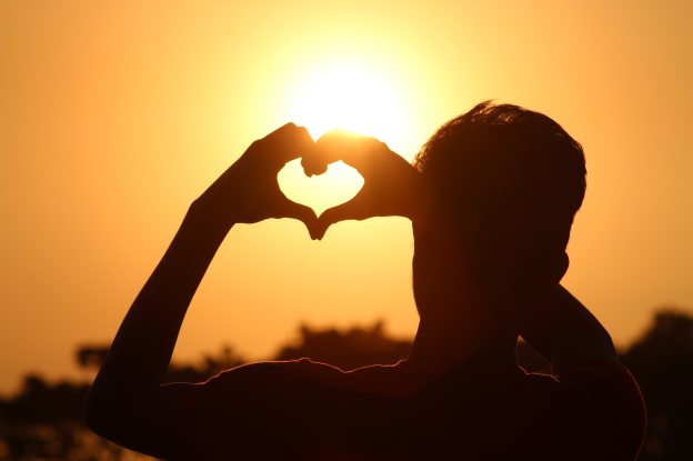 Man making heart shape with hands towards the sky.